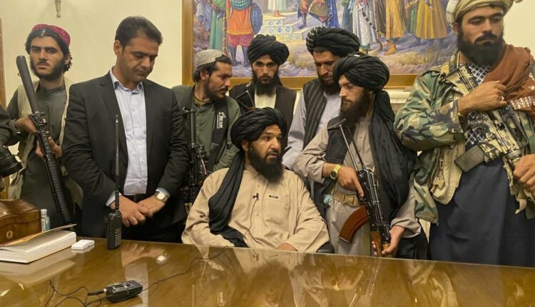 Taliban fighters take control of Afghan presidential palace after the Afghan President Ashraf Ghani fled the country, in Kabul, Afghanistan, Sunday, Aug. 15, 2021. Person second from left is a former bodyguard for Ghani.